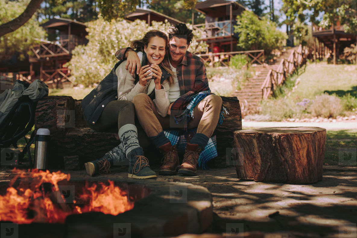 Loving couple resting by a bonfire at campsite