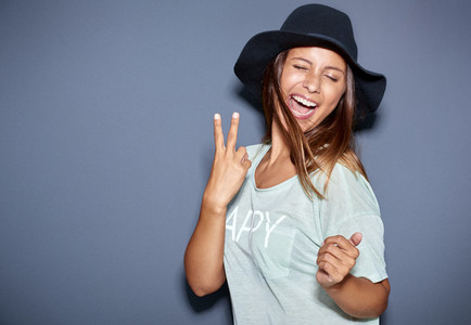 Hipster fashionable young woman giving a V sign