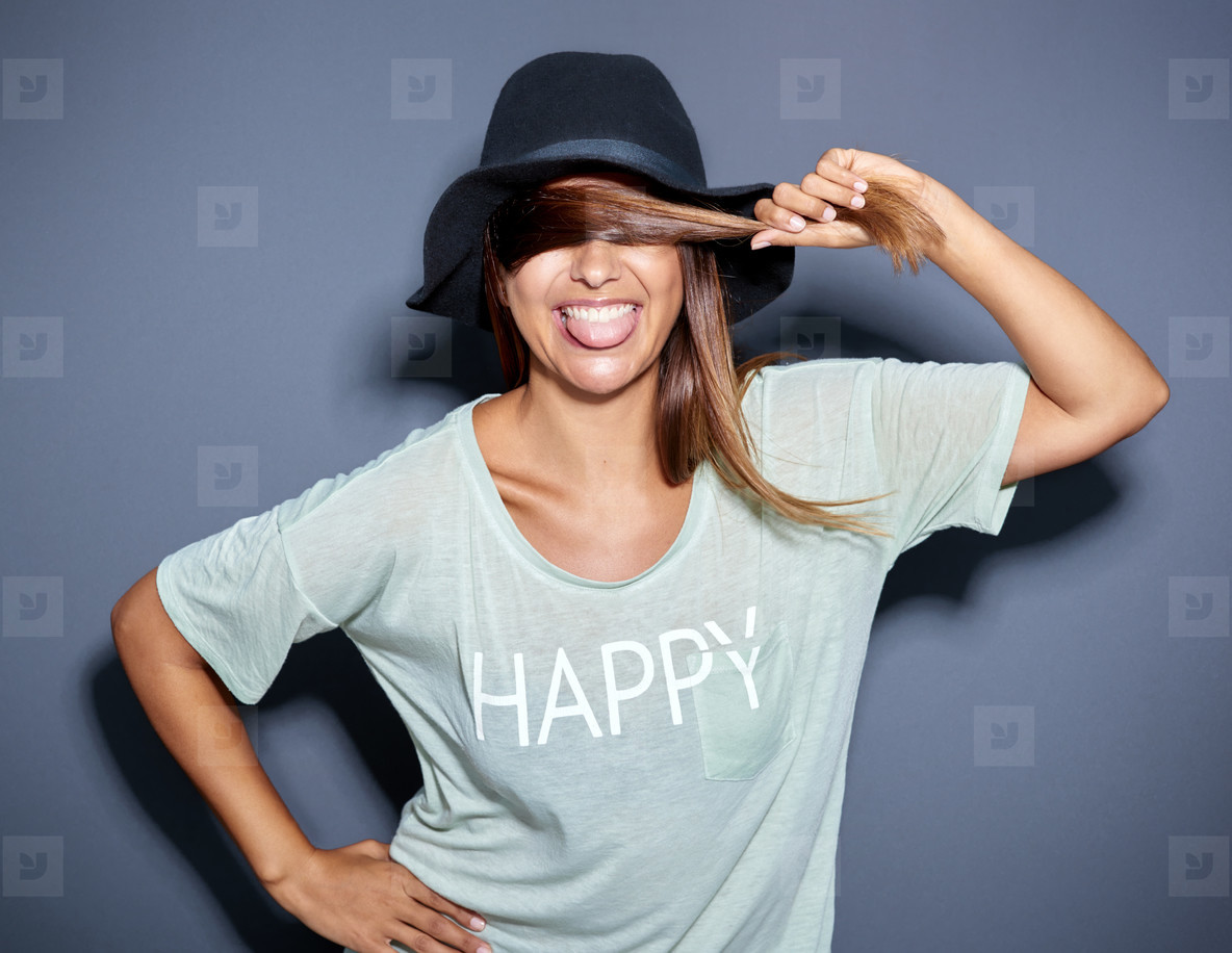 Lively happy young woman sticking out her tongue