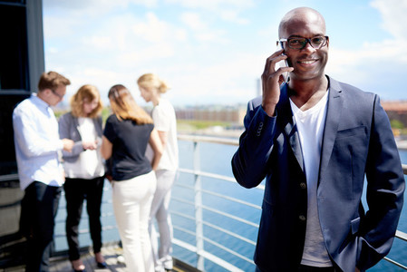 Black male executive smiling while on cellphone