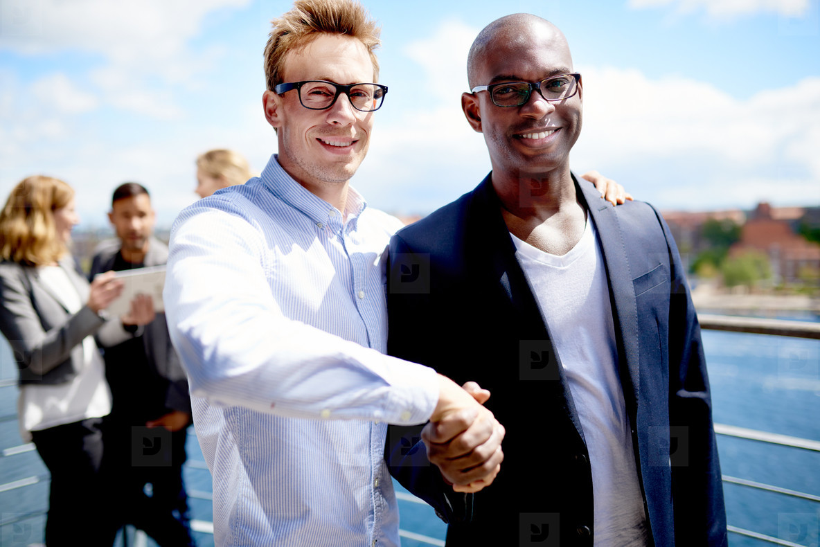 White colleague and black colleague shaking hands