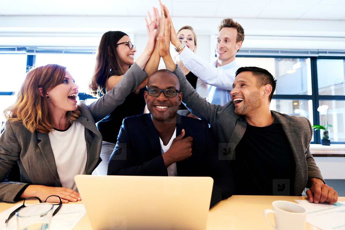 Group of executives high fiving over colleagues head