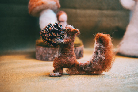 Felt squirrel holding a pine cone