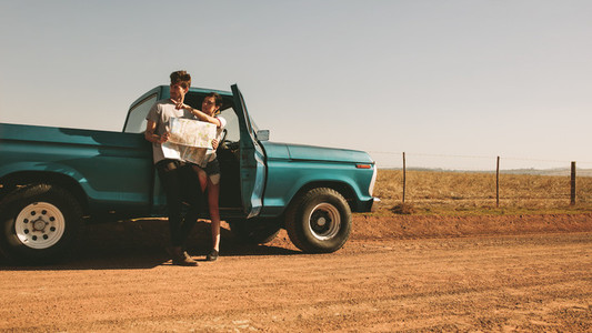 Couple on a road trip looking at map for navigation