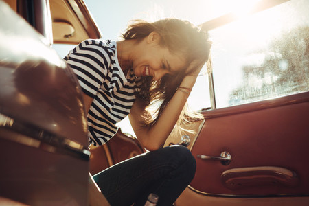 Woman sitting in the car and laughing