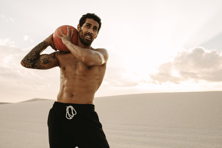 Athlete exercising with medicine ball on sand dunes