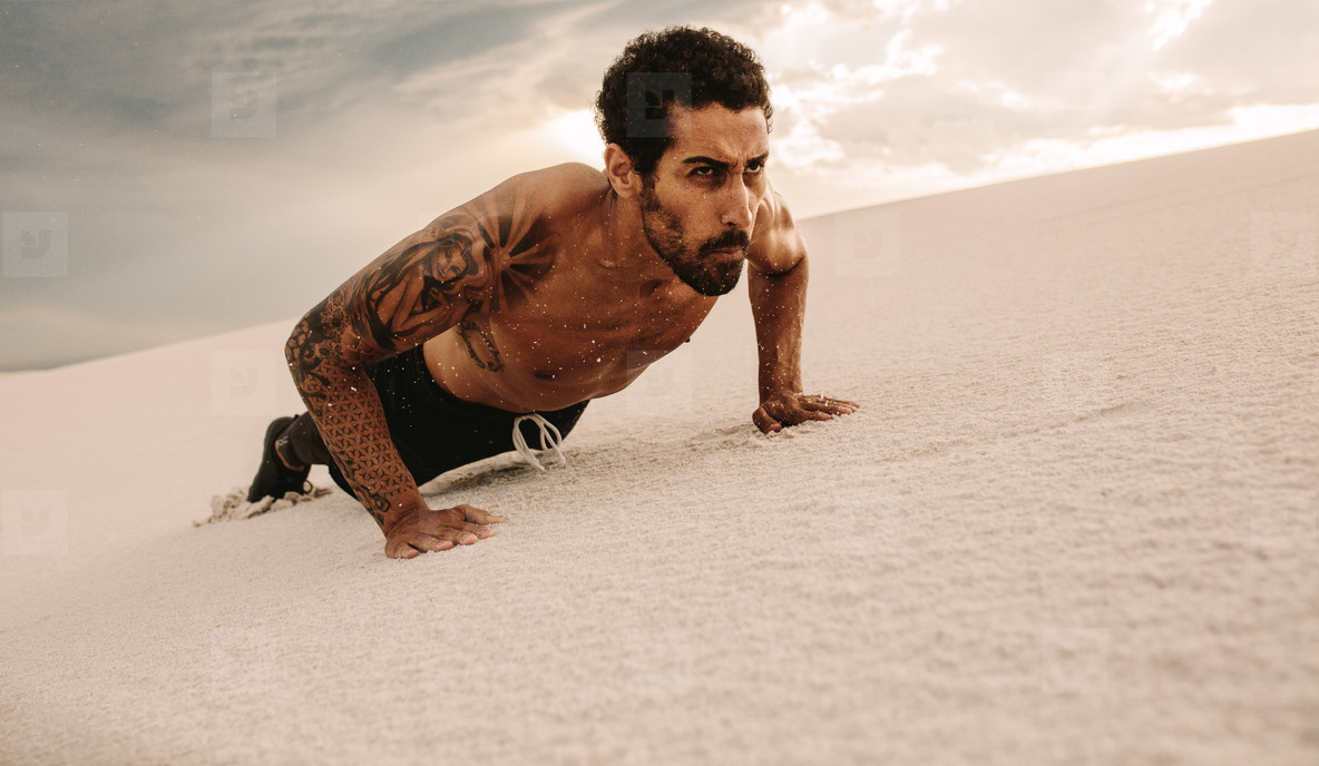 Fit man doing push ups over sand dune