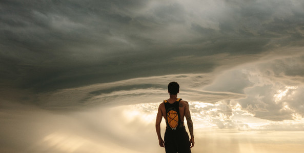 Fit man taking rest after workout against dramatic sky