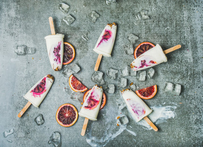 Blood orange yogurt and granola popsicles on ice concrete background