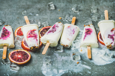 Red orange  yogurt  granola popsicles on ice cubes  healthy dessert