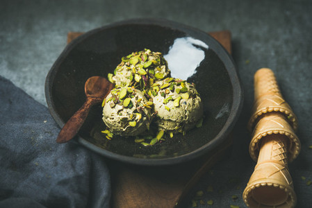 Homemade pistachio ice cream scoops with crashed nuts in plate