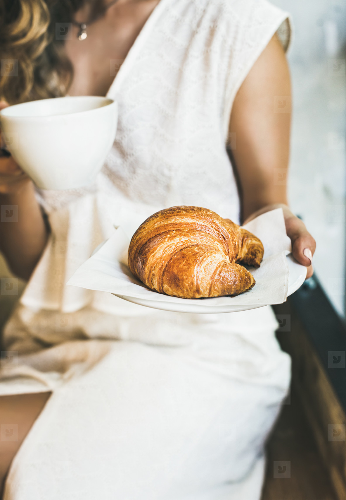 Young blond woman holding fresh croissant and cup of cappuccino