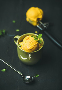 Mango sorbet ice cream scoops with fresh mint