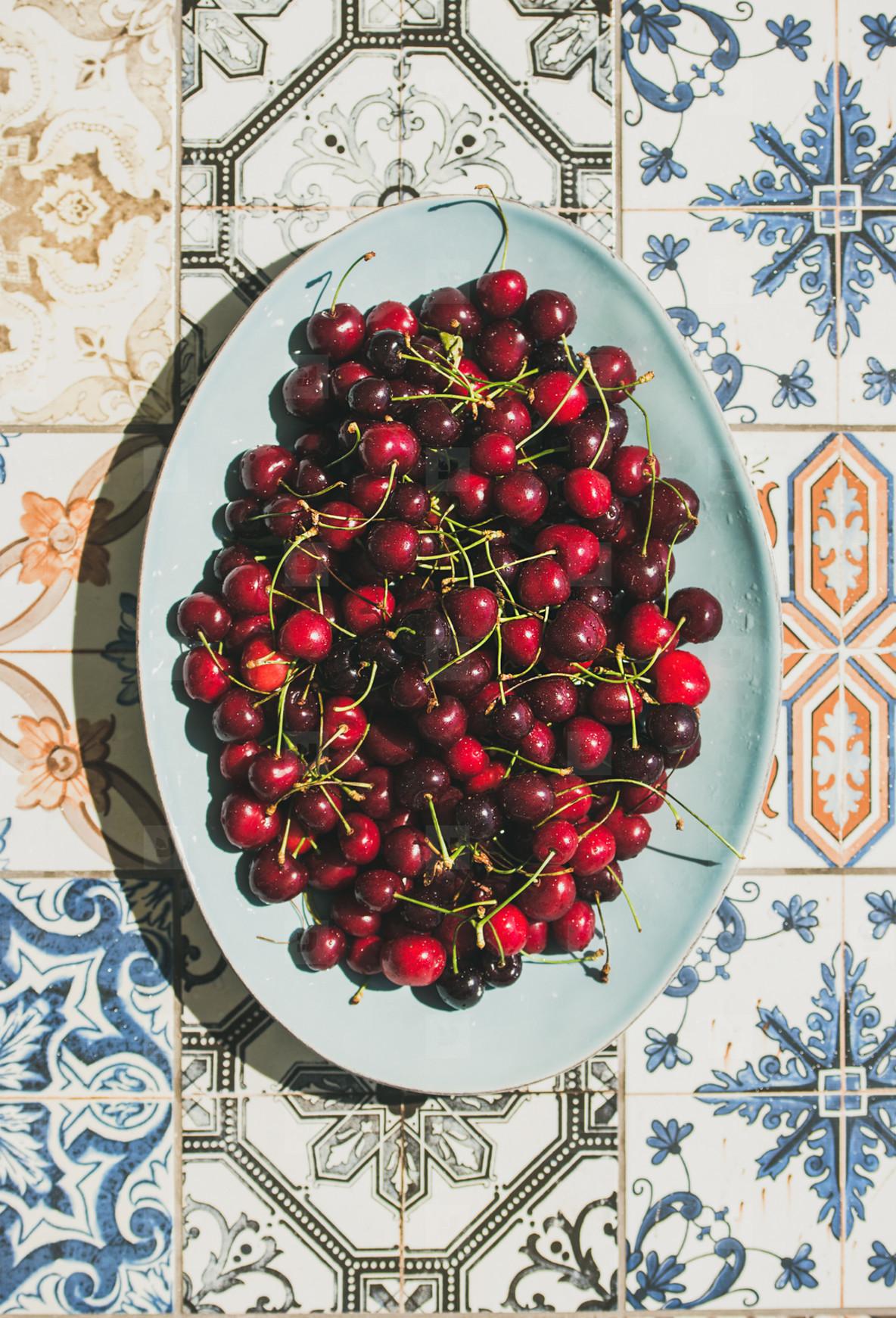 Fresh sweet cherries over oriental ceramic tiles background  top view