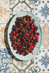 Fresh sweet cherries over oriental ceramic tiles background top view