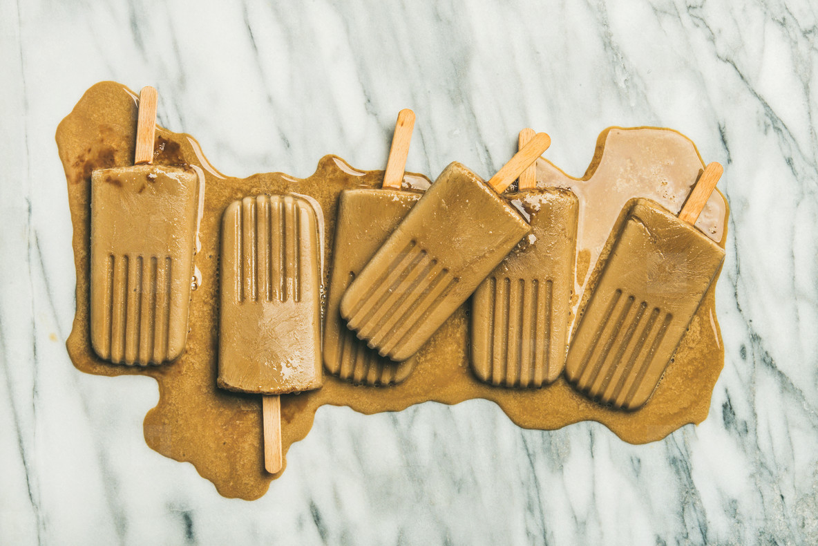Flatlay of melting coffee latte popsicles on marble background