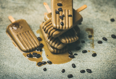Flatlay of melting coffee latte popsicles with beans