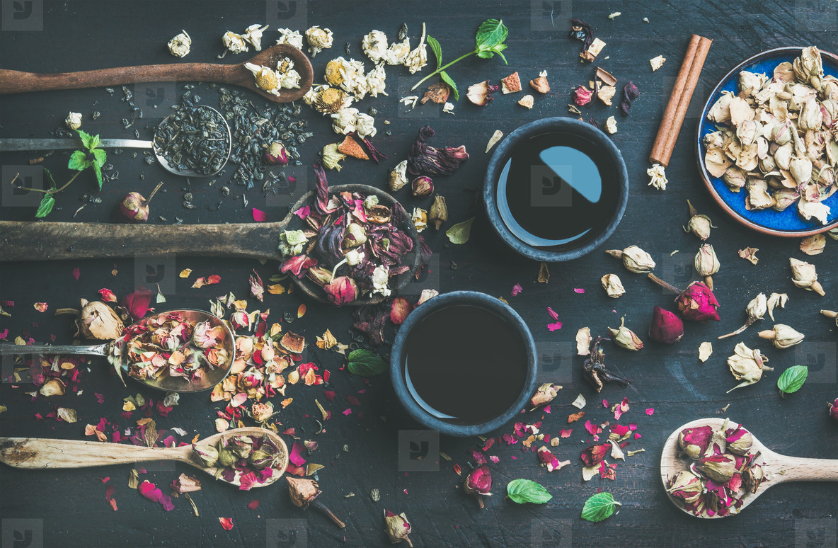 Chinese black tea and wooden spoons with herbs and buds