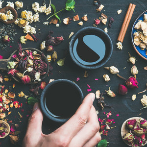 Chinese black tea and spoons with herbs and buds