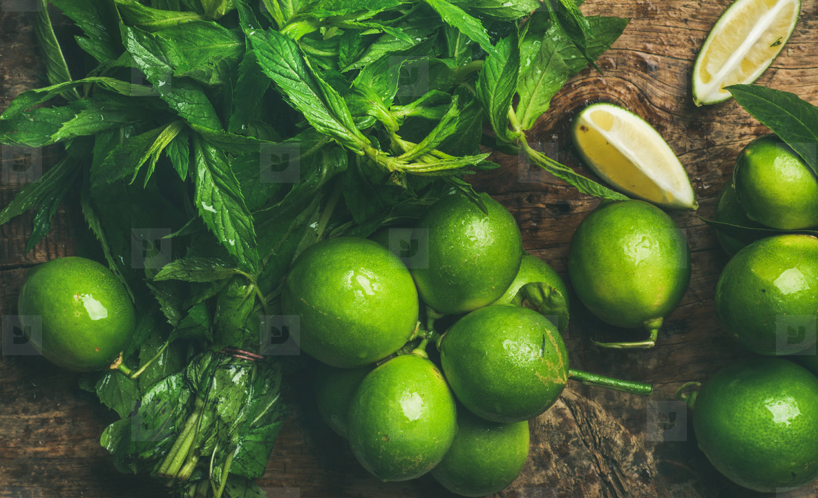 Flatlay of fresh limes and mint for making summer drinks