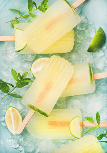 Summer lemonade popsicles with lime and chipped ice  top view