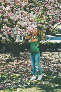 Young woman in casual clothes smelling magnolia flowers