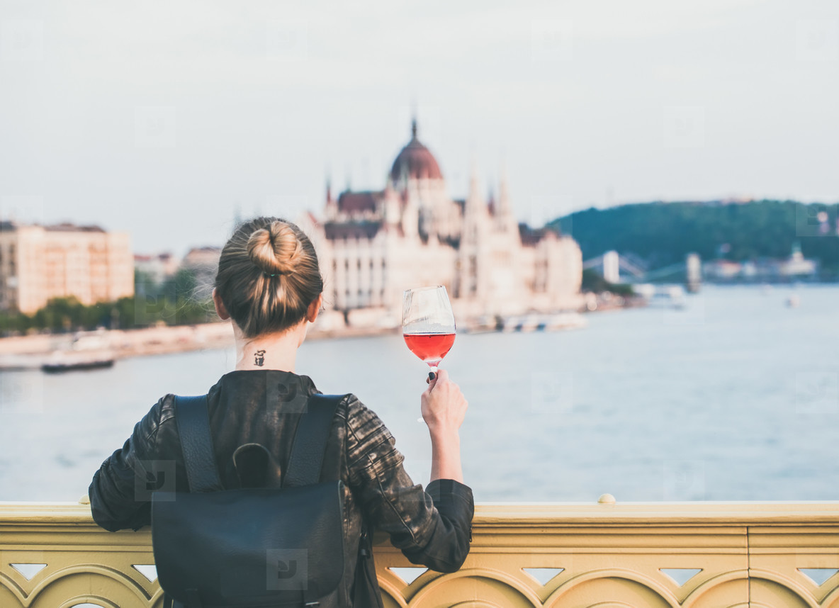 Young woman standing with glass of rose wine in Budapest