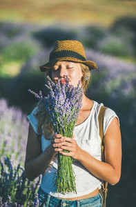 Young girl wearing straw hat enjoying bouquet of lavender flowers