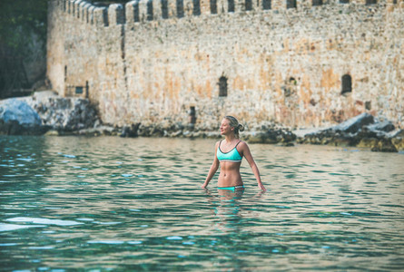 Young woman relaxing in sea at beach near fortress wall