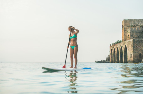 Young beautiful european woman tourist practicing paddle boarding Alanya Turkey