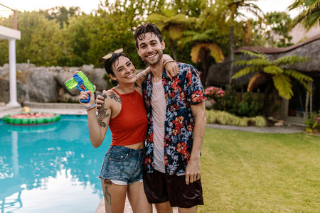 Cheerful couple by the pool with water gun