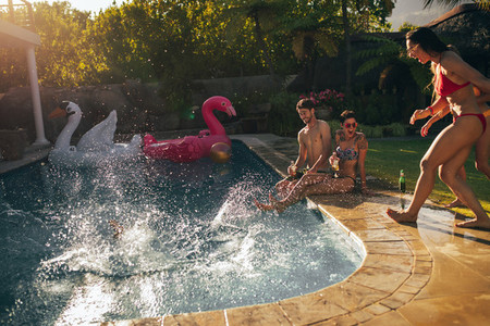 Group of young people enjoying at poolside party