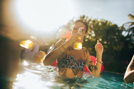 Woman having beer with friends in pool party