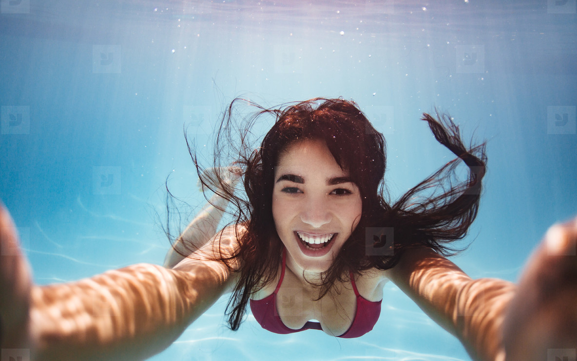 Woman swimming underwater and taking selfie