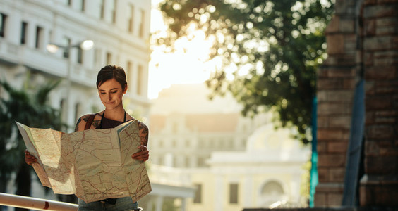 Woman standing outdoors holding a map