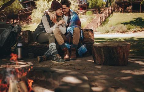 Romantic couple sitting near bonfire at campsite