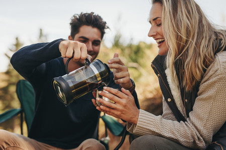 Couple having coffee at a campsite
