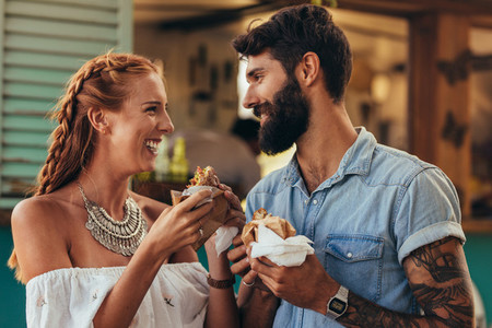 Couple enjoying eating food truck burger