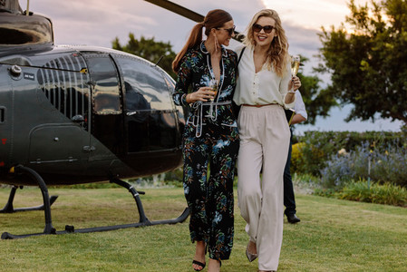 Women friends walking away from helicopter with wine