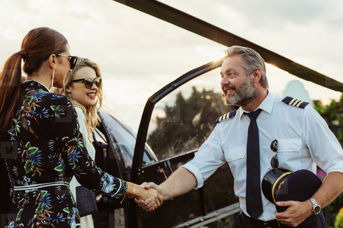 Helicopter pilot shaking hands with two women