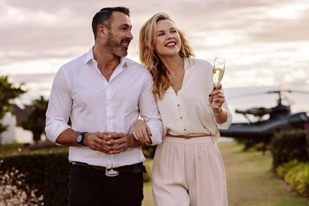 Elegant couple walking outdoors with wine