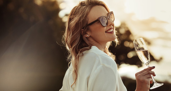 Smiling woman in sunglasses drinking wine