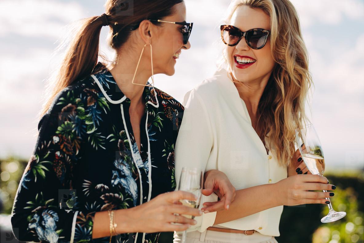 Stylish female friends walking outdoors