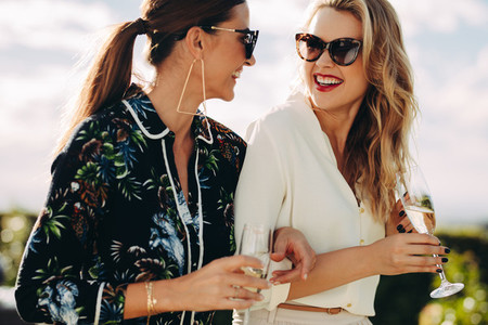 Stylish female friends walking outdoors
