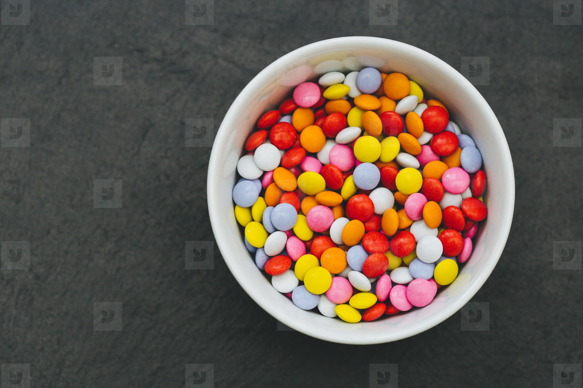 Bowl of candy sweets dark background