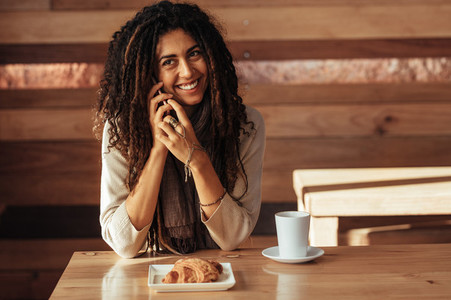 Woman talking over mobile phone at a cafe