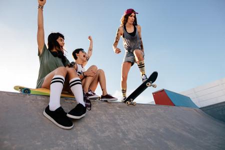 Girl practising skateboarding with friends cheering
