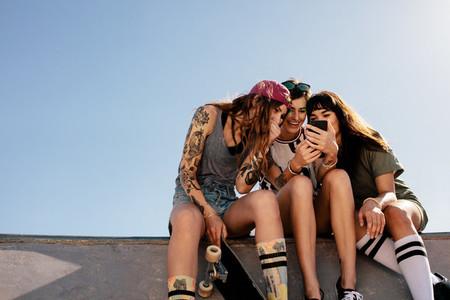Female skaters sitting at skate park using smartphone