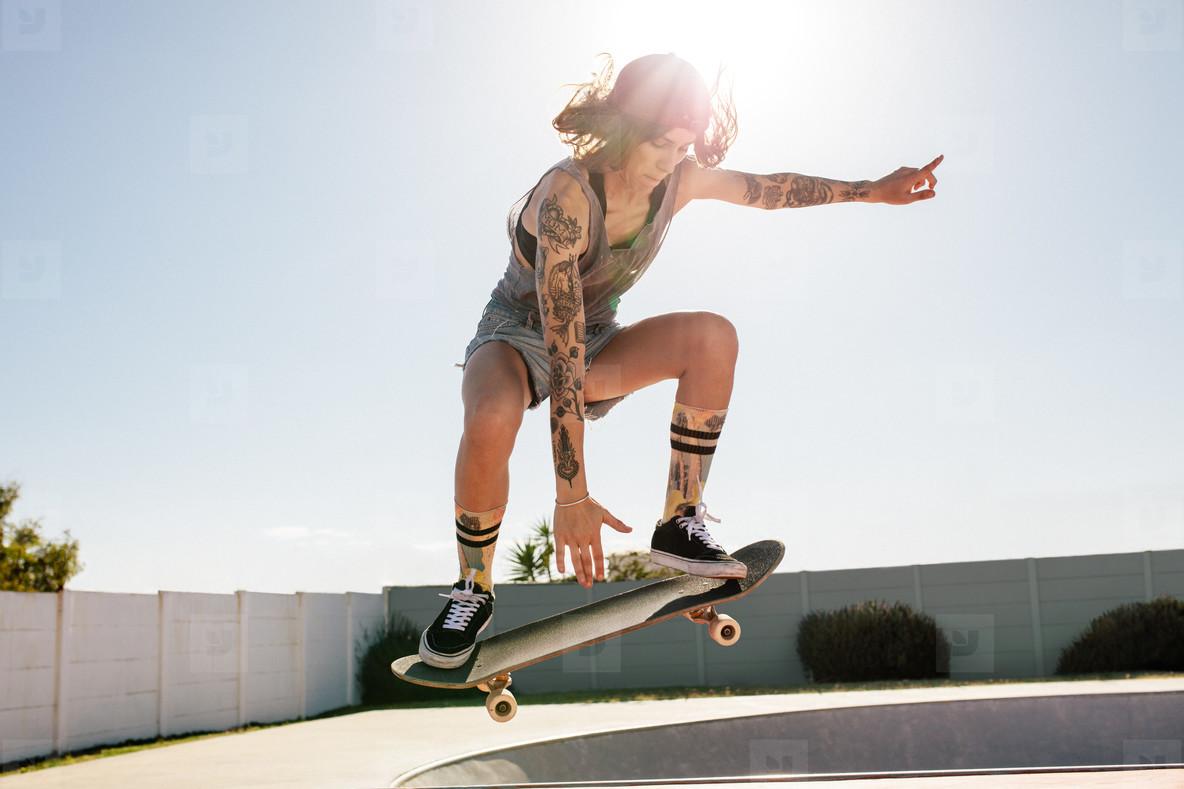 Women skater doing ollie on skateboard
