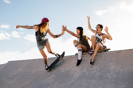 Skater girl riding skateboard at skate park with friends